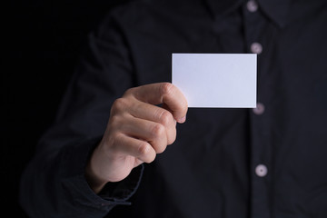A man in business black suit holding a white blank business card,name card.