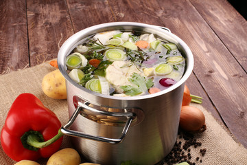 Broth with carrots, onions various fresh vegetables in a pot - c