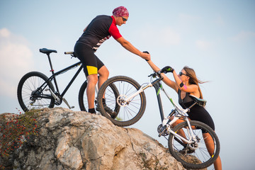 Bicyclist helping to his partner, pulling the hand woman with a mountain bike into steep hill against evening blue sky. Adventure travel on bike.
