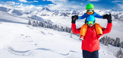 Little boy having fun with his caucasian attractive father in Kitzbühel ski resort, Tyrolian Alps