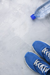 Flatlay sports composition with blue sneakers and bottle of wate