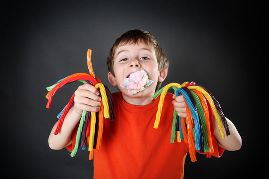 Young boy holding colorful licorice candy with a mouthful of cot