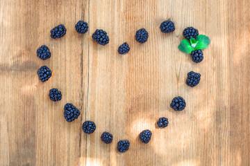 Blackberries on wooden deck heart shape love