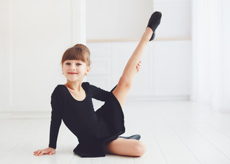 beautiful young girl doing stretching exercises at ballet school