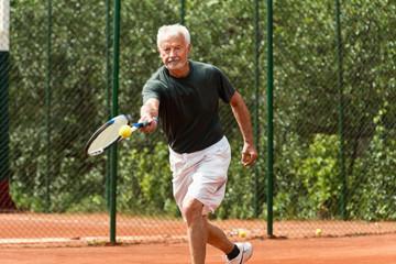 Senior tennis player. Senior man exercising tennis