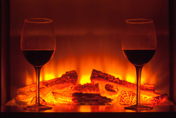 Two glasses of wine next to the fireplace.