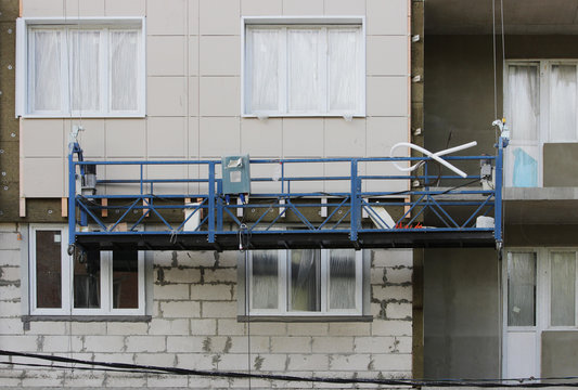 work with blue front two suspended cradle without workers on a newly built high-rise building.