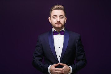 Handsome man in tuxedo and bow tie looking at camera. Fashionable, festive clothing. emcee on dark background