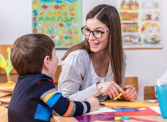 Kindergarten Teacher Works With Child