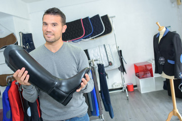 Man in shop holding riding boot