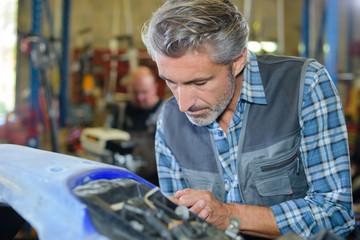 mechanic working on car body