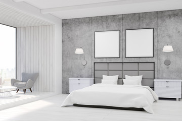 Bedroom interior with concrete walls, a large bed with two square posters hanging above it and an armchair near a panoramic window with wooden panels. 3d rendering. Mock up.