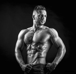 Young male fitness model poses on isolated background showing his perfect abs