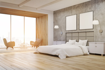 Side view of a bedroom interior with concrete walls, a large bed with two square posters hanging above it and two bedside tables. 3d rendering. Mock up. Toned image
