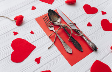 Valentine's Day.cutlery and felt heart on a wooden background