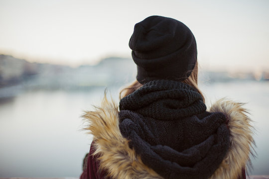 Back view of a sad hipster girl against blurred winter background