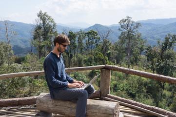 Homme et ordinateur portable en haut d'une montagne