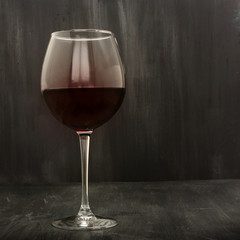 Glass of red wine on black with copyspace
