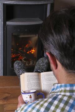 Mann liest Buch vor Kamin, Tasse Kaffee