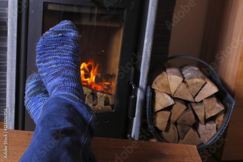 übereinandergeschlagene füße vor kamin, gemütlich