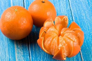 three tangerine on a blue wooden background