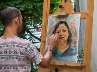 Artist painting portrait of asian woman,oil color on canvas