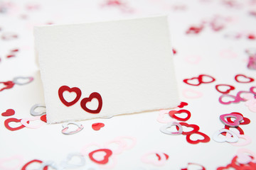 Valentines day greeting card on a white background with red and pink hearts confetti