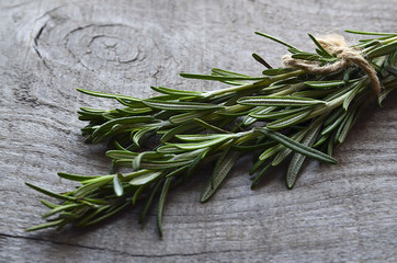 Fresh green rosemary herb on old wooden background.Rosemary herb.Rosemary bound on a wooden table.Selective focus.