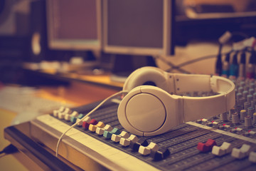 Headphones lying on the mixing console in vintage colors