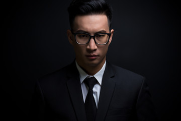 Businessman in black suit on isolated black background