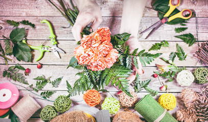 Hands of female florist arranging flower bouquet over a wooden table. Workplace of the florist. Vintage toning. Top view