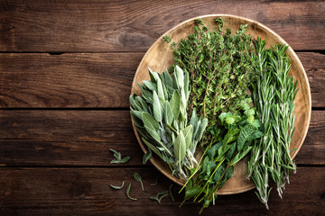 Photo sur Toile Condiment various fresh herbs, rosemary, thyme, mint and sage on wooden background