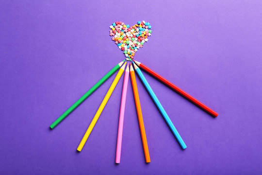 Colorful sprinkles with pencils on the purple background