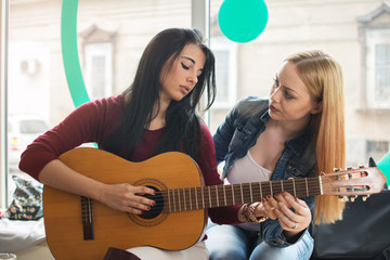 Girl teaching her friend to play guitar.