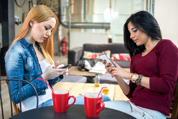 Girlfriends using smartphones at a cafe.