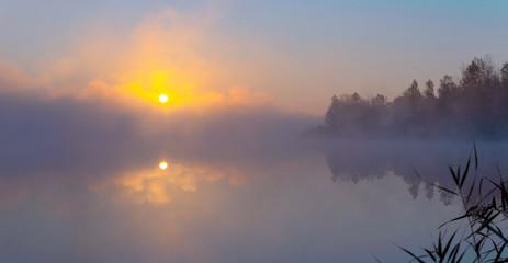 Panorama of beautiful foggy lake coast at sunrise moment.