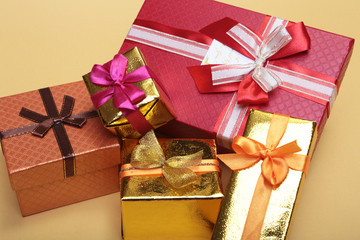Beautiful gold present box with red bow and ribbons on backgound
