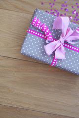 Pacco regalo con fiocco rosa su tavolo di legno