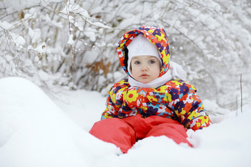 Little cheerful girl on a winter walk in the snow