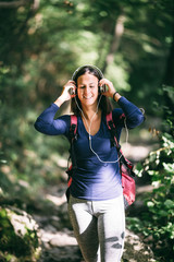 Beautiful sporty woman enjoying in untouched nature hiking and outdoors adventure. She standing in the forest and listening to music with headphones.