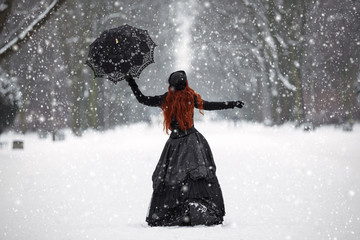 Mysterious red-haired woman in Victorian dress in the winter par