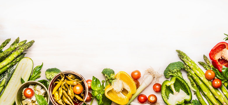 Variety of organic vegetables ingredients with asparagus and feta for delicious seasonal cooking , white wooden background, top view, place for text, banner