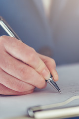 Hand of young businesswoman signing business contract agreement