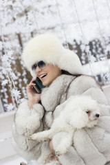 Beautiful woman making a phone call while holding her dog outdoors. Winter time. Woman wearing a white fur coat. Christmas decorations in the background.