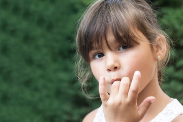 Portrait of brunette little girl licking her fingers outdoors. Girl is looking at the camera.