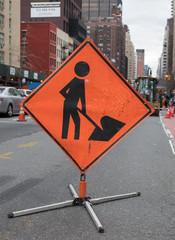 Orange Construction Sign of Man Shoveling on City Street