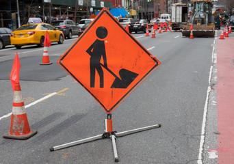 Orange Construction Sign of Man with Shovel on City Street