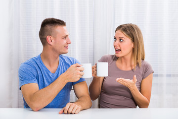 Young happy couple enjoys drinking coffee,talking and laughing together.