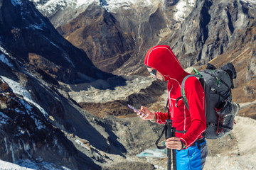 Alpine Climber using smart Phone in high Mountains