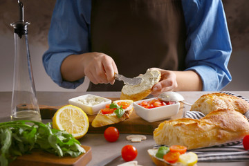 Woman making delicious traditional bruschetta on kitchen table
